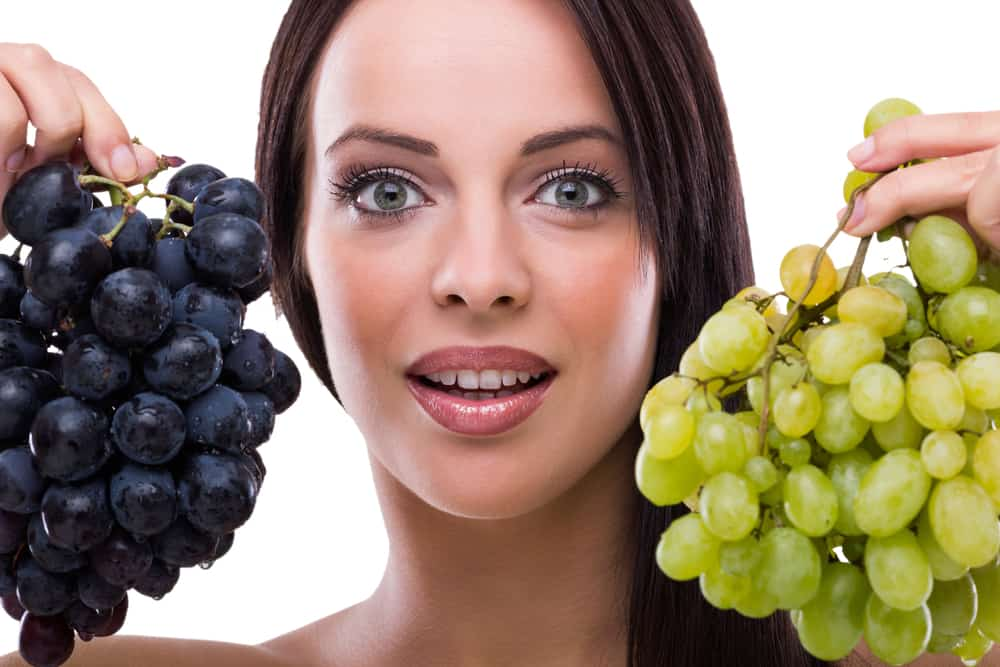 woman holding red and green grapes