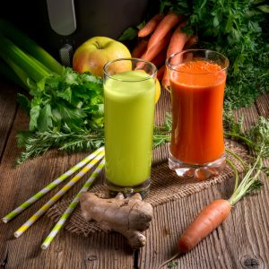 freshly squeezed vegetable juices with two glasses and assorted vegetables
