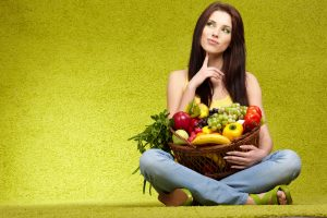 woman holding basket of healthy fruit and vegetables