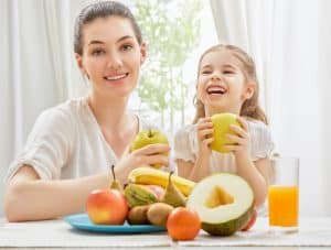 what can you juice for better health woman and child with fruit and veggies and glass of juice