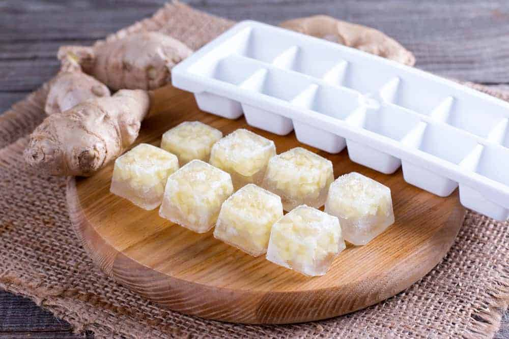 8 ice cubes of ginger juice on chopping board with empty ice cube tray and ginger roots showing how to make ginger juice frozen ice cubes