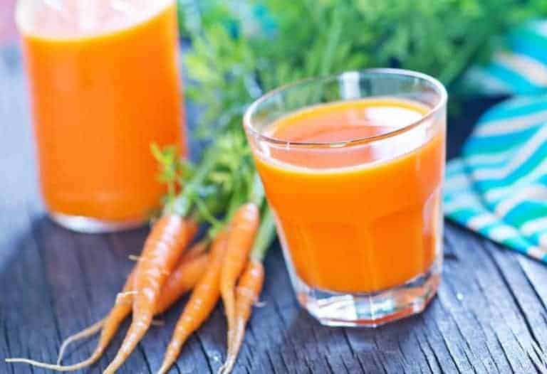 homemade juice with two glasses of carrot juice with 5 raw carrots on a wooden table