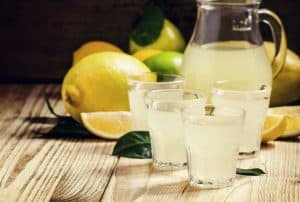 3 glasses of juice made at home and a pitcher of juice surrounded by lemons and other fruit